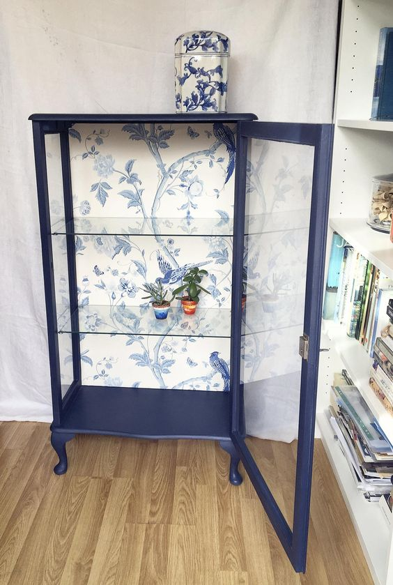 a navy glass display cabinet with beautiful blue printed wallpaper inside is a very chic and cool idea to rock