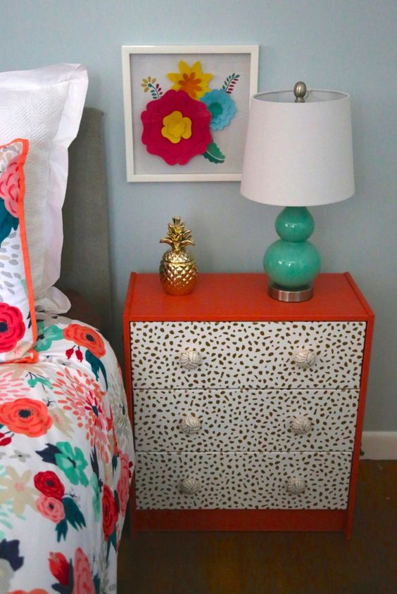 a bright red nightstand with drawers covered with Dolmatin print wallpaper is a very fun and cool idea