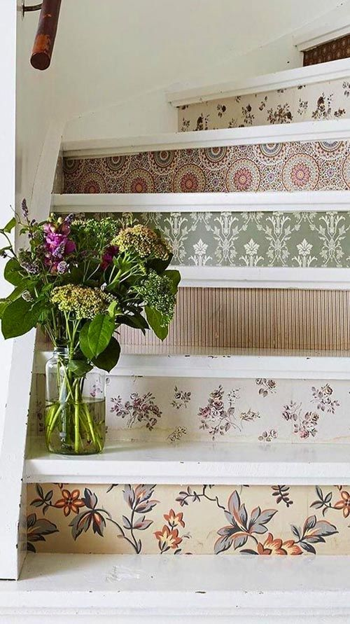 a vintage white staircase refreshed with beautiful wallpaper risers, all different ones and in different muted tones