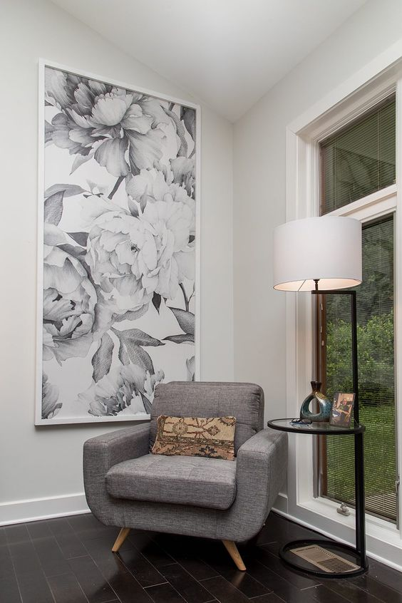a cozy little nook with floral wallpaper as a framed artwork, a chic grey chair and a glass table with a lamp