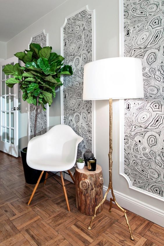 a blank wall filled in with matching wallpaper pieces framed as artworks is a simple and great idea