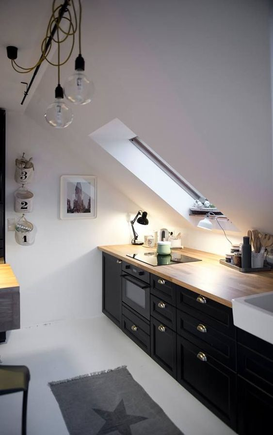a Nordic attic kitchen with black cabinetry, butcherblock countertops, pendant lamps and a skylight plus a printed rug