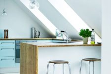 a Nordic attic kitchen with blue cabinets, a white kitchen island, butcherblock countertops and cool stools