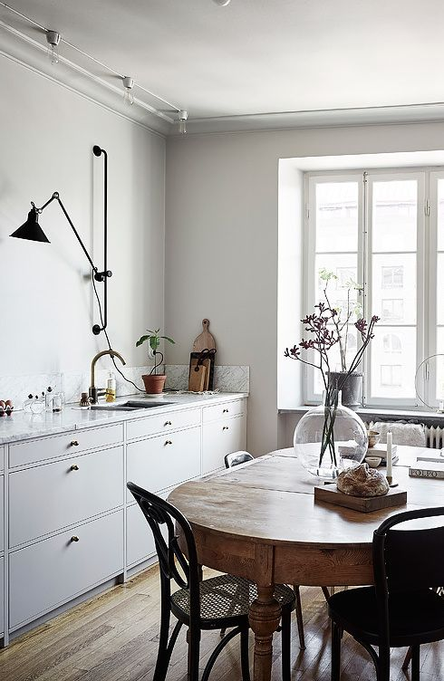 a Nordic kitchen with white walls and a bamboo floor, grey cabinets, a vintage table and rattan chairs, touches of black for a more modern feel