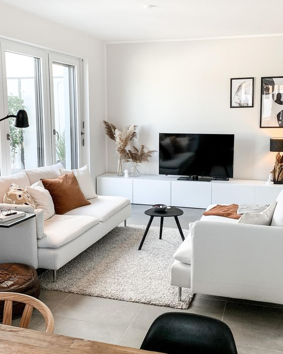 a Nordic living room with white sofas, sleek storage unit, a black mini table, various pillows and a gallery wall