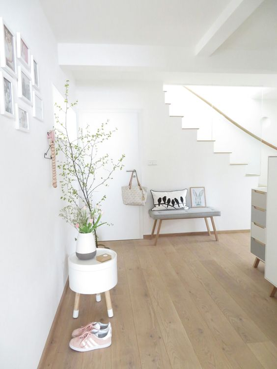 a Nordic space with white walls and light-colored laminate flooring, grey and white furniture, potted plants and blooms