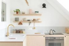 a Scandinavian attic kitchen with light stained plywood cabinets, white countertops, open shelves, a skylight and gold touches