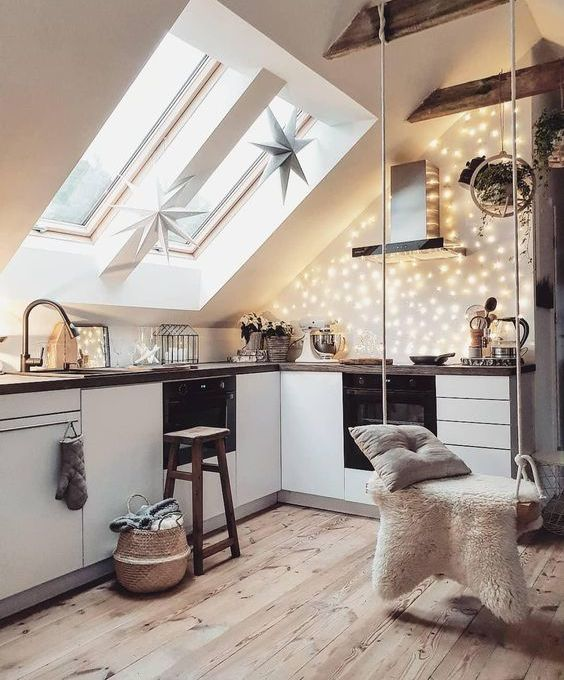 a Scandinavian attic kitchen with sleek white cabinetry, dark stained countertops, lights, stars and a swing for a dreamy touch