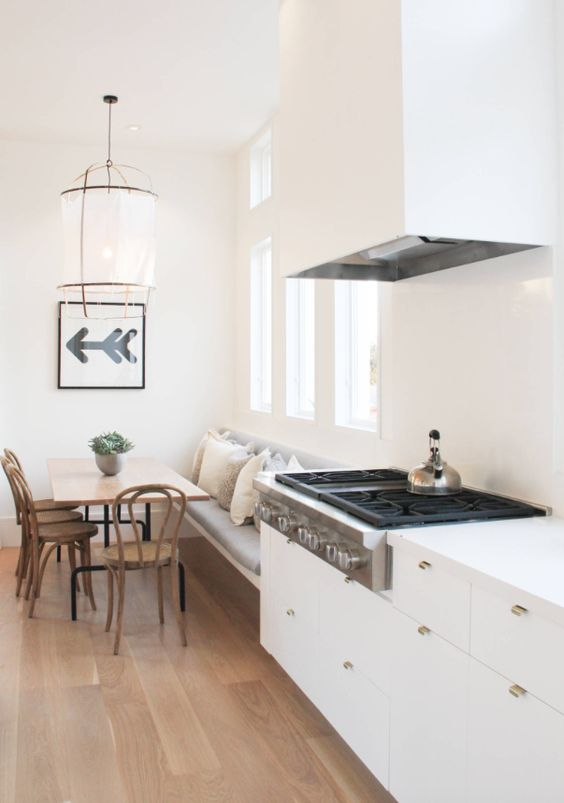 a Scandinavian kitchen with a bamboo floor, white sleek cabinets and a matching hood, a floating bench, a table and chairs