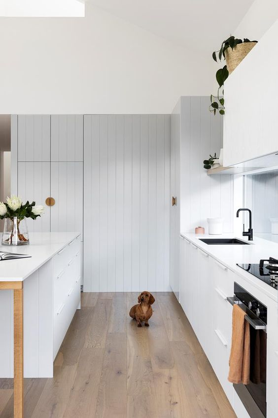 a Scandinavian kitchen with white and light grey planked cabinetry, laminate floors, baskets and black fixtures is very chic