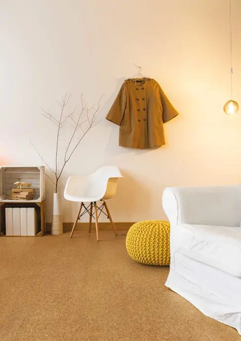 a Scandinavian room with white walls and a cork floor, a white sofa, crate storage units, a white chair and a yellow ottoman