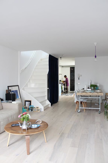 a Scandinavian space with bamboo floors, a grey sofa and a low table, a table on casters and a white staircase is cool and fresh