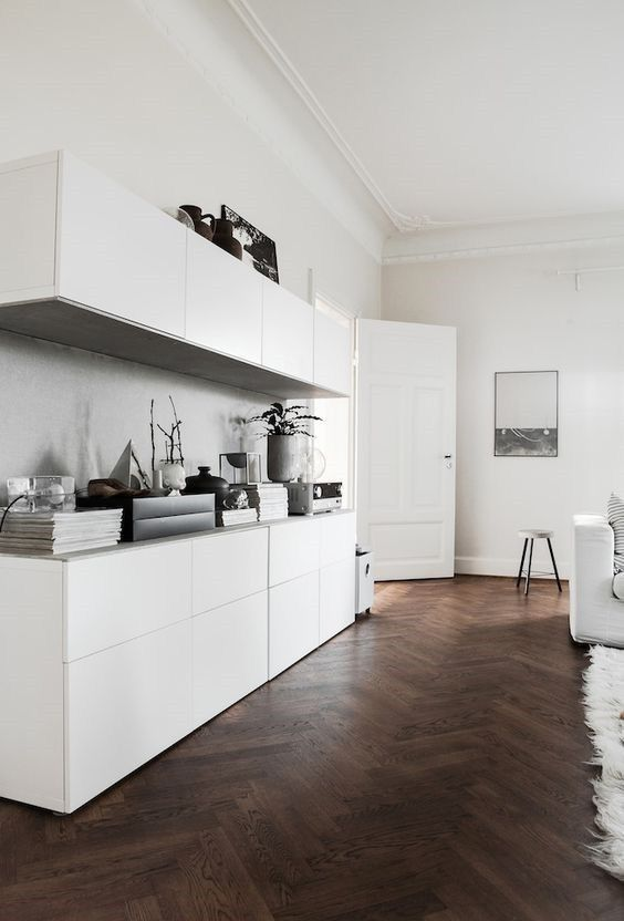 a Scandinavian space with dark stained parquet flooring, sleek white cabinets, white furniture and some art and accessories