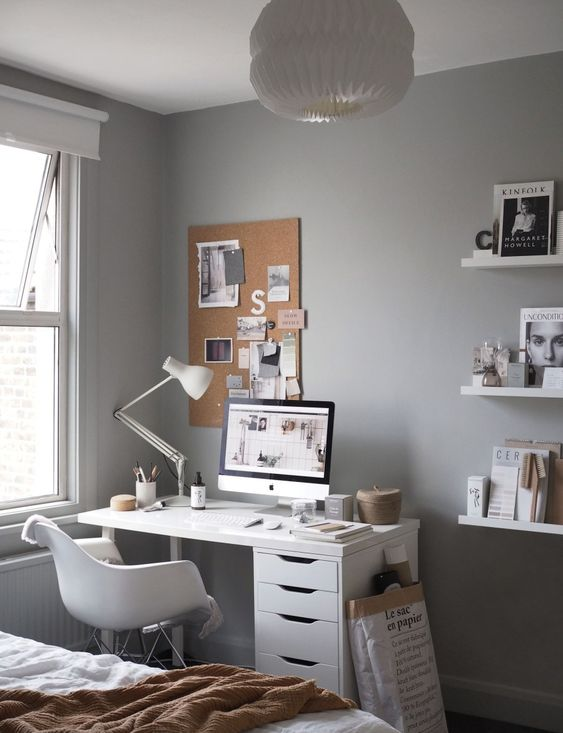 a Scandinavian space with grey walls, white furniture, open shelves with various books and magazines, a cozy working nook in the corner