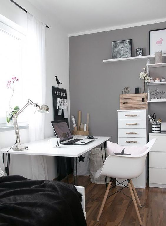 a Scandinavian space with white and grey walls, white furniture, black bedding, a shelving unit, a lovely workspace by the window