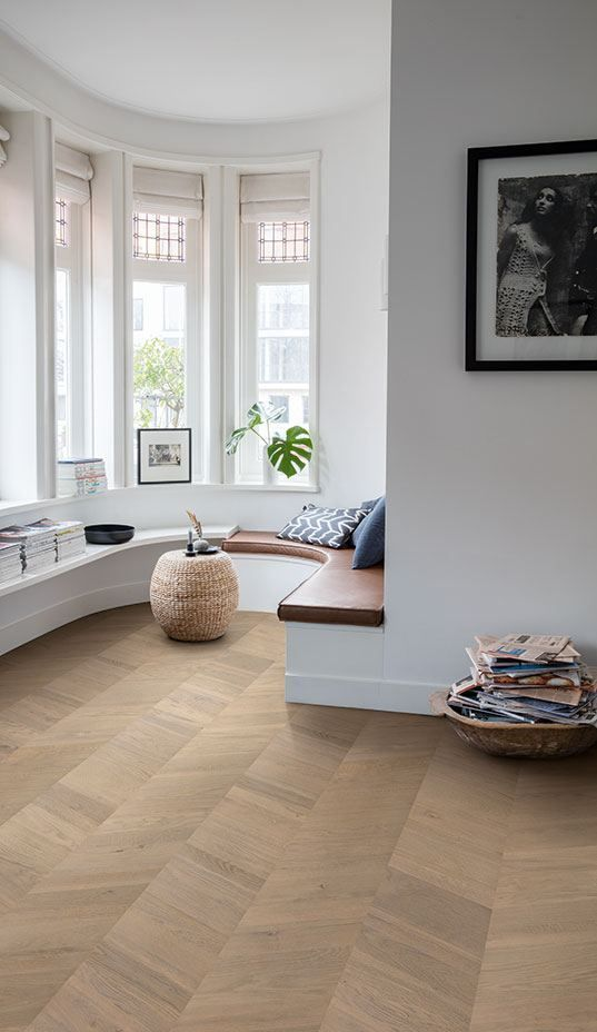 a Scandinavian space with white walls, a bow window, a parquet floor, a curved space with an ottoman and some books