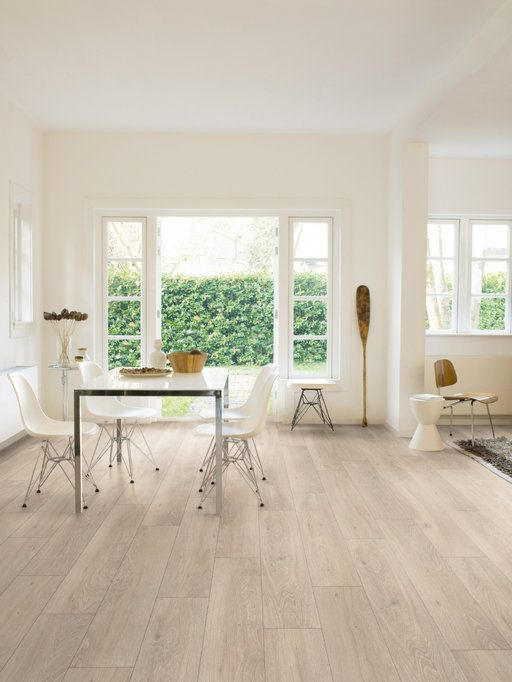 a Scandinavian space with white walls and light laminate floors, a glass table and white chairs, lots of natural light inside