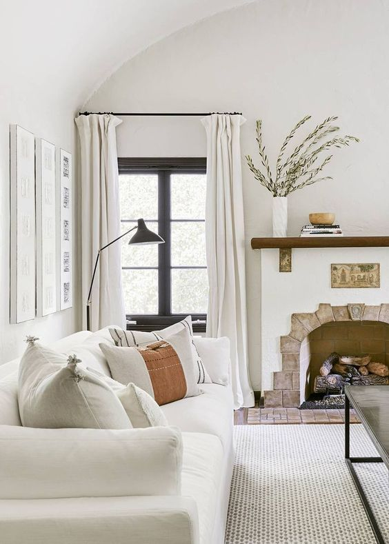 a Spanish farmhouse living room with a fireplace and a mantel, a low coffee table, a white sofa and a neutral rug, neutral curtains