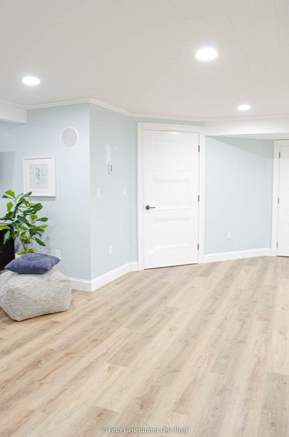 a basement space with vinyl flooring that imitates stained wood, light blue walls and some ottomans is welcoming