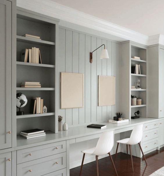 a beautiful aqua-colored home office with a beadboard wall, built-in storage units and a double desk, a sconce and chairs