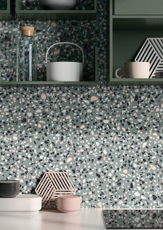 a beautiful grey terrazzo backsplash that matches green shelves and white countertops and looks cool and bright