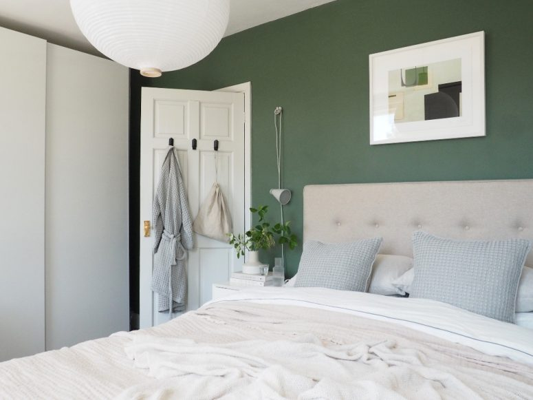 a bedroom with green walls and neutral furniture, a green artwork and potted greenery plus a paper lamp
