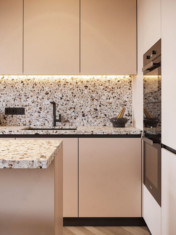 a blush minimalist kitchen with terrazzo countertops and a backsplash, black fixtures and built-in lights is chic and pretty