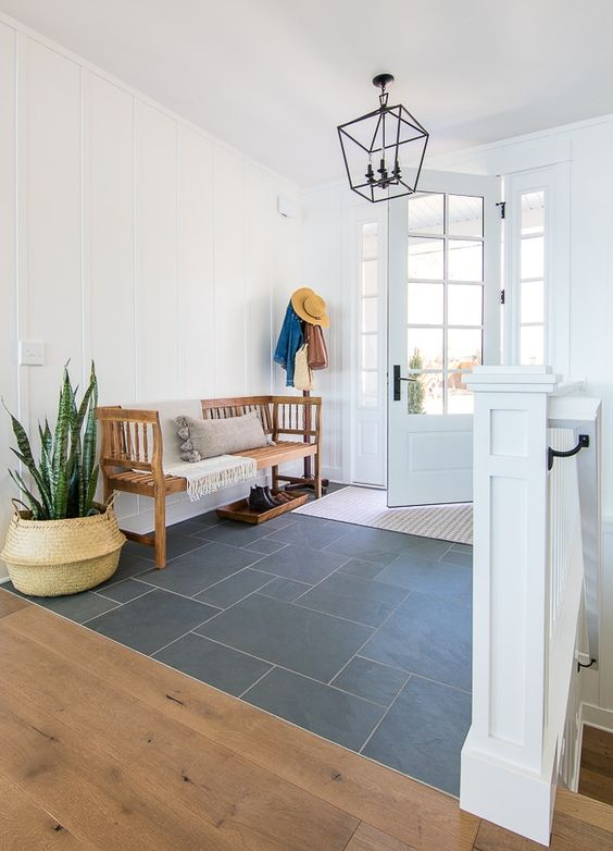 a boho entryway with a tile floor, a wooden bench, a potted plant, a pendant lamp and a lovely French door is very chic