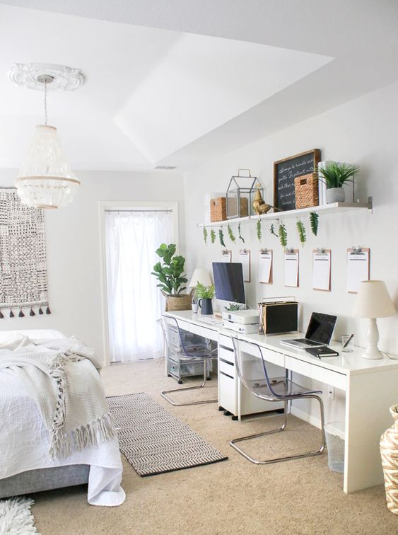 a boho neutral bedroom with a large bed, a shared long desk, sheer chairs, an open shelf and potted greenery and boho decor