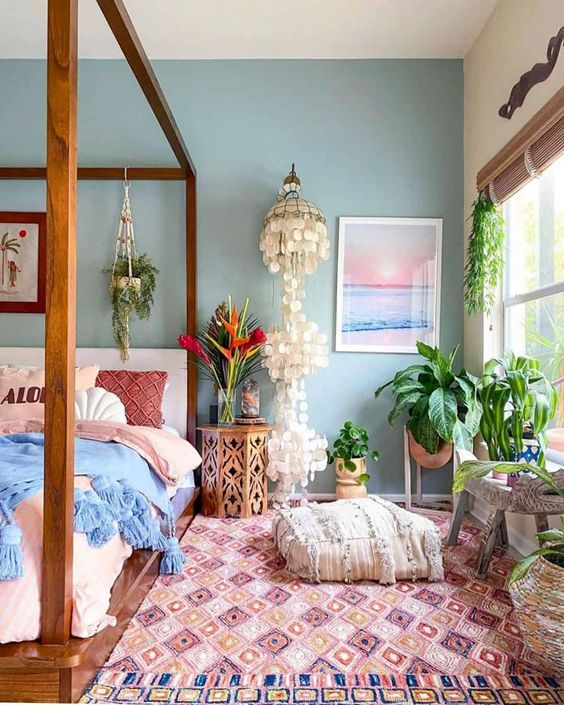 a boho summer bedroom with a canopy bed, a printed rug, pink and blue bedding, potted plants, a mother of pearl chandelier