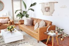 a boho summer living oom with amber sofas, a low coffee table, woven poufs, a macrame piece and some potted plants