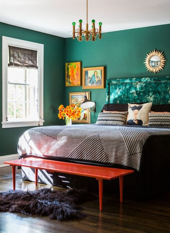 a bold bedroom with green walls and a green upholstered bed, printed bedding, a colorful gallery wall, a chic chandelier and a red bench