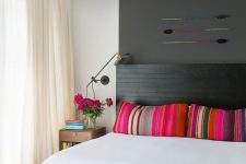 a bold summer bedroom with a black bed, a grey accent wall and ceiling, colorful pillows and a rug and a turquoise bench