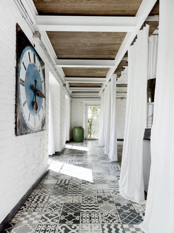 a breezy and airy entryway with grey and white patchwork style tiles on the floor give interest to the space and make it relaxed