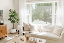 a breezy neutral summer living room with creamy sofas, a rattan cabinet, a coffee table, a potted plant and neutral textiles