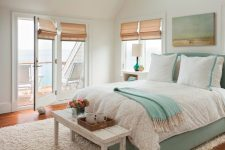 a breezy summer bedroom with an aqua-colored bed, an aqua artwork, a white bench and shades on the windows