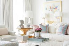a breezy summer living room with white and grey furniture, pastel pillows and a lovely gallery wall, a crystal chandelier and an acrylic coffee table