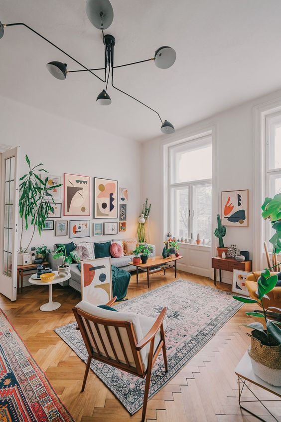 a bright modern living rom with a grey sofa, chic furniture, a bold gallery wall, potted plants and a boho rug