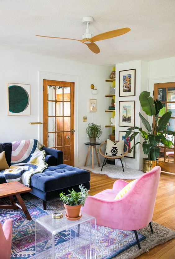 a bright summer living room with a navy sectional, hot pink chairs, a gallery wall, an acrylic table and potted plants