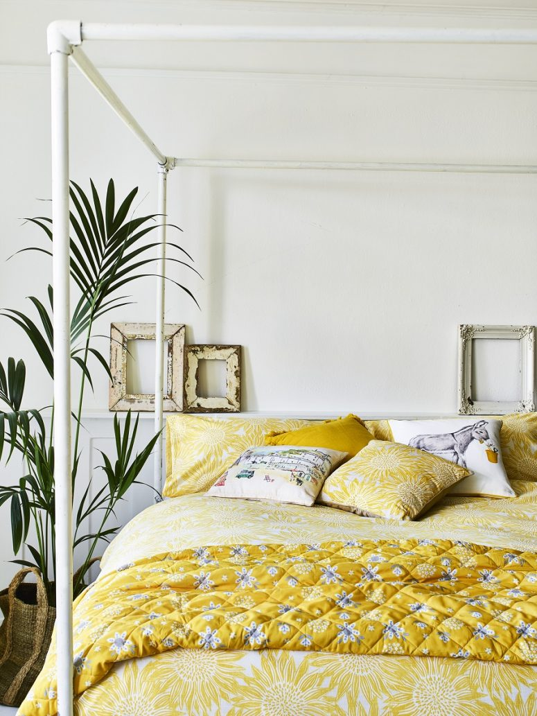 a cheerful bedroom done in neutrals, with a canopy bed and bright yellow floral bedding plus a potted plant feels summer-like