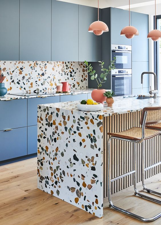 a cheerful blue kitchen with a bright terrazzo backsplash and countertops plus coral pendant lamps and pots