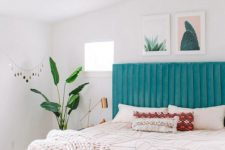 a cheerful modern bedroom with a blue upholstered bed, pink chairs, neutral textiles, a chandelier and a potted plant