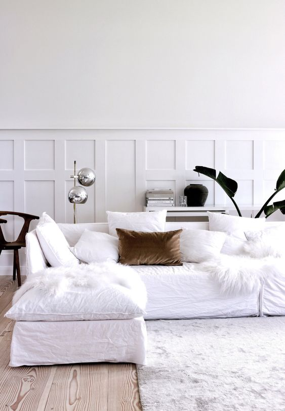 a chic Scandinavian living room with paneling, a white sectional, white pillows, a stylish floor lamp and some plants