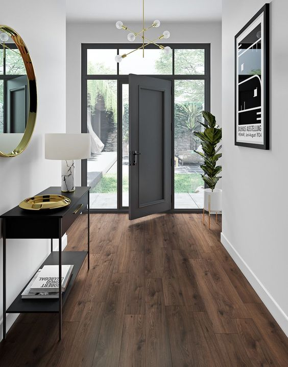 a chic and refined entryway with white walls and dark laminate flooring, a black console and a round mirror in a gilded frame