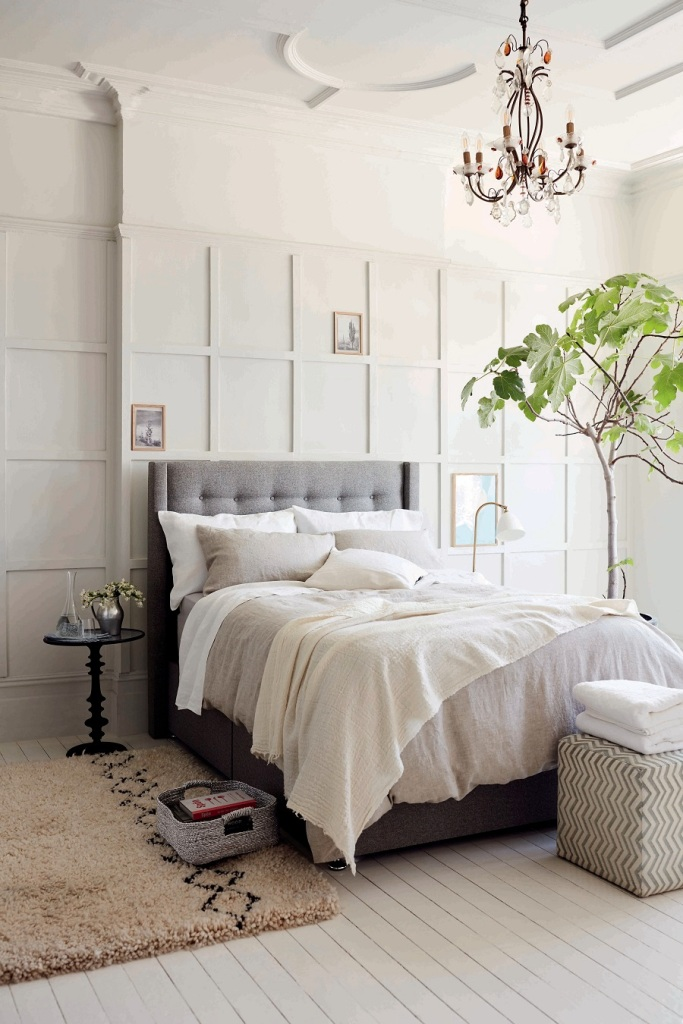 a chic and refined neutral bedroom with a paneled wall, a grey bed and a printed ottoman, a crystal chandelier and a potted plant