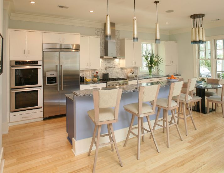 a chic coastal kitchen with bamboo floors, white cabinets, a blue kitchen island, rattan stools and pendant lamps