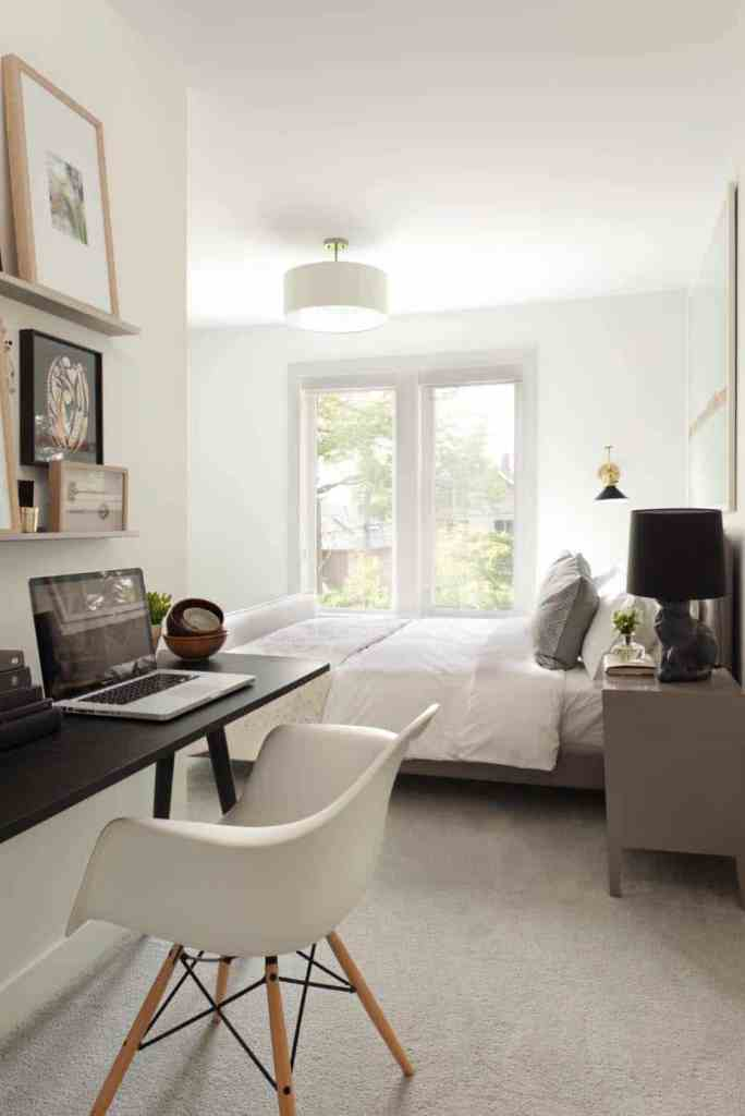 a chic contemporary bedroom with an upholstered bed and a small workspace nook with a ledge gallery wall and a white chair