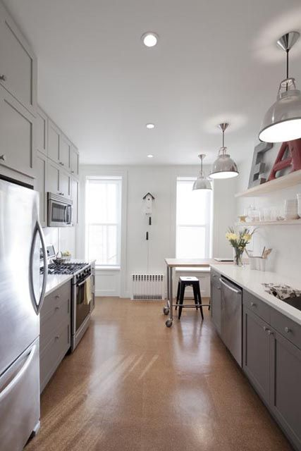 a chic farmhouse kitchen in grey, with a white backsplash and countertops, a cork floor, pendant metal lamps and built-in lights