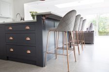 a chic farmhouse kitchen with white cabinetry and a navy kitchen island, tall grey stools and copper touches is chic