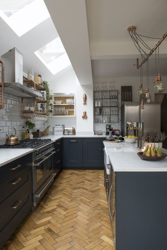 a chic farmhouse kitchen with white walls and white subway tiles, light stained parquet flooring, graphite grey cabinets, skylights